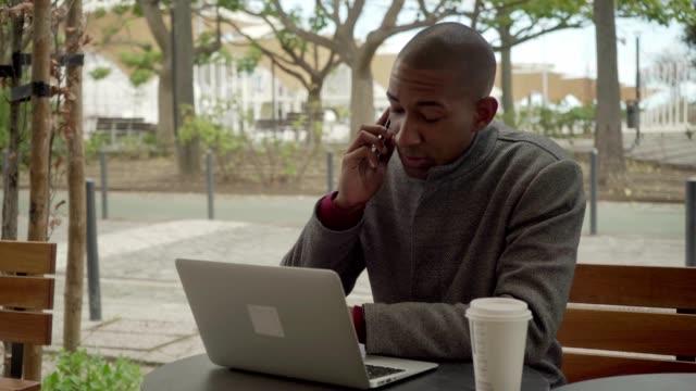 vídeos de stock e filmes b-roll de young freelancer using smartphone and laptop computer outdoor - esplanada portugal