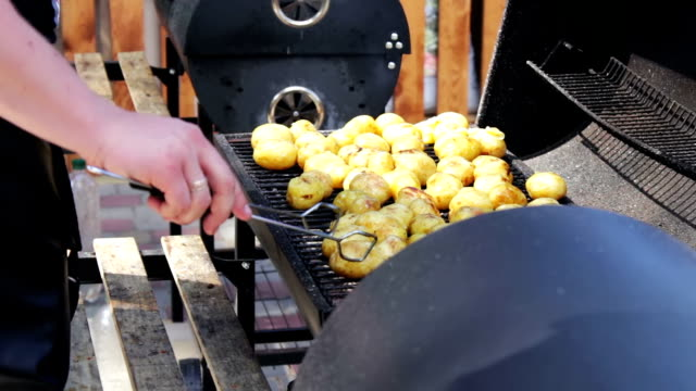 young fresh potatoes are grilled. bbq on street - smażony ziemniak filmów i materiałów b-roll