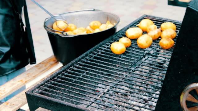 young fresh potatoes that are laid out and turned over on a barbecue grill on picnic - smażony ziemniak filmów i materiałów b-roll