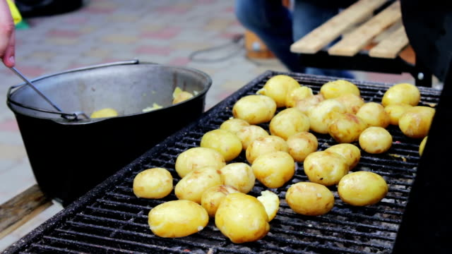 vídeos de stock e filmes b-roll de young fresh potatoes that are laid out and turned over on a barbecue grill on picnic - comida salgada