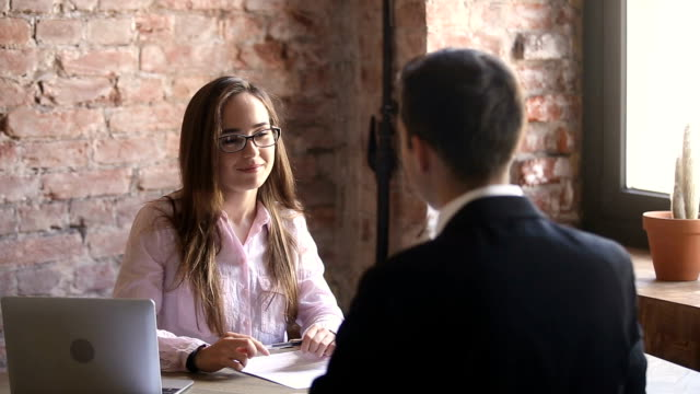 Young friendly hr manager holding interview with candidate in office video