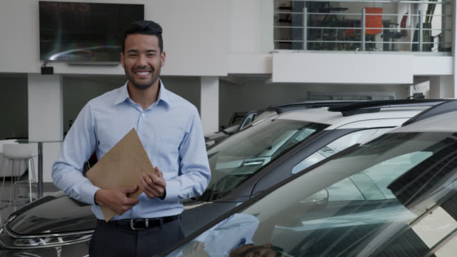 Young friendly salesman at a car dealership holding a clipboard facing camera smiling Young friendly salesman at a car dealership holding a clipboard facing camera smiling - Sales concepts car salesperson stock videos & royalty-free footage