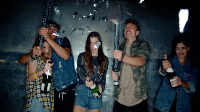Young friends celebrating at night time with champagne and confetti video