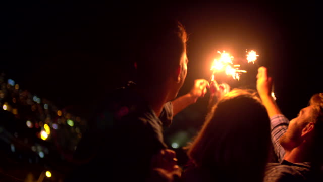 Young friends celebrating on the rooftop with sparklers video