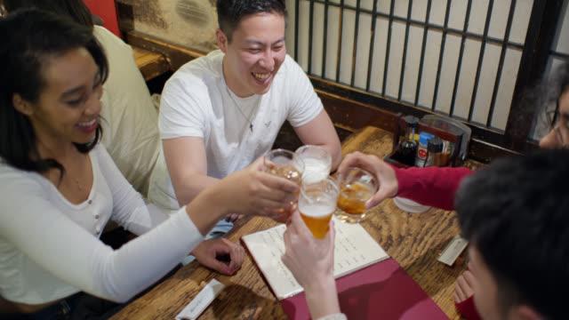 東京バーでお酒を飲む若い友達 - ビール点の映像素材/bロール