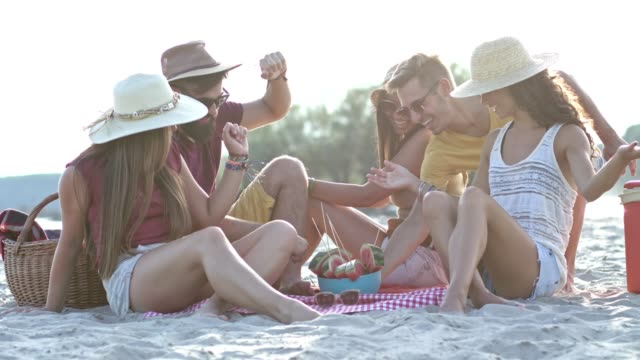 young friends eating watermelon on beach - picnic stock videos and b-roll footage