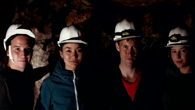 vídeos de stock, filmes e b-roll de exploradores de jovens amigos, olhando para a câmera em uma caverna escura - característica arquitetônica