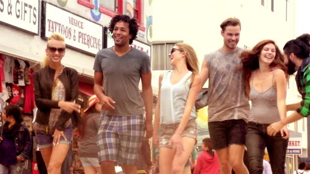 スローモーションの若い友人のグループで楽しくベニスのビーチ、ロサンゼルス。 ビデオ