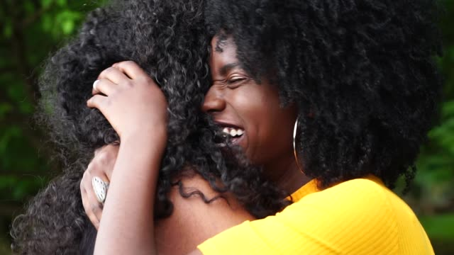 young friends girls embracing in the park - chiedere scusa video stock e b–roll