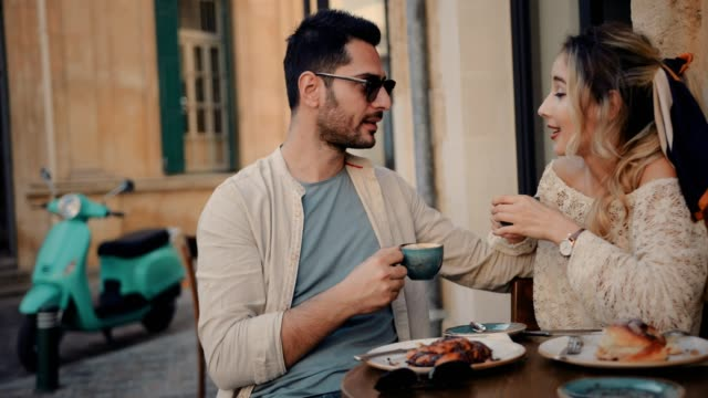 Young friends having breakfast and drinking coffee at traditional cafe video