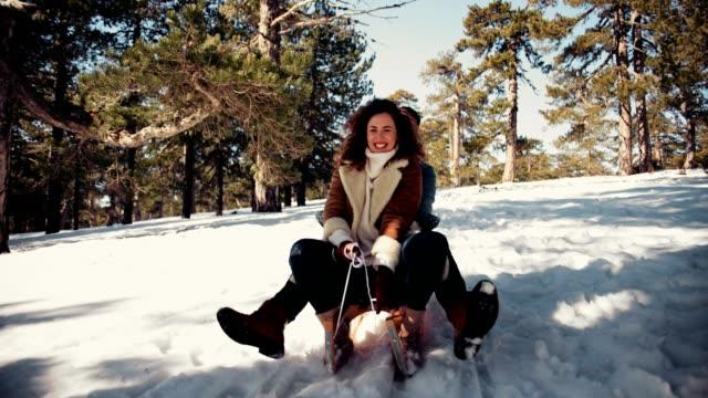 unga vänner har roligt kälkåkning ner snöiga berg kulle - vintersport bildbanksvideor och videomaterial från bakom kulisserna
