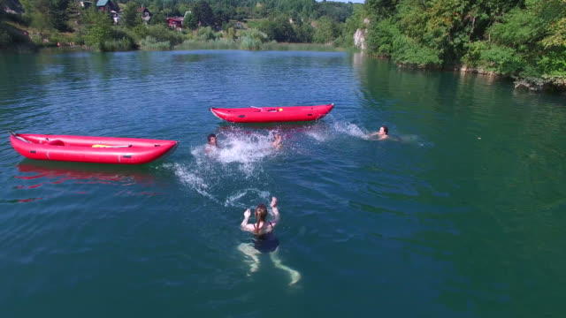 Young friends having fun swimming in river and splashing each other with water video