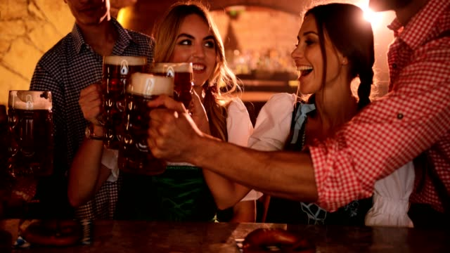 Young friends in German costumes celebrating Oktoberfest with beer video