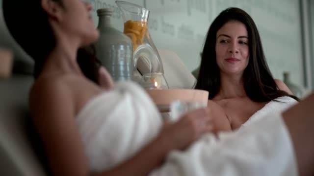 junge freunde in handtücher gemeinsam entspannen im wellnesscenter - sauna und nassmassage stock-videos und b-roll-filmmaterial