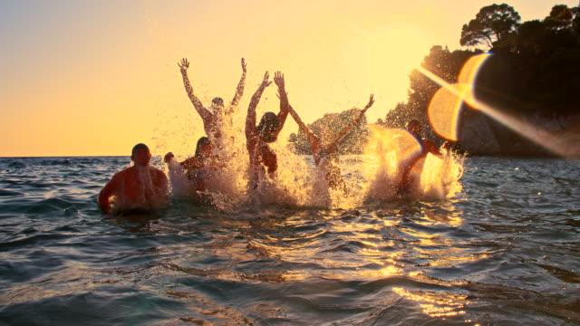 Una persona jóvenes amigos saltar fuera del mar - vídeo