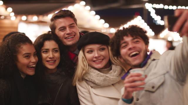 若い友人のクリスマス マーケットで Selfie のポーズ ビデオ