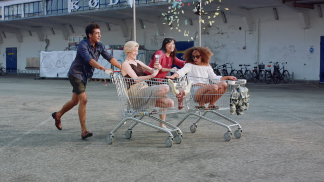 Young friends racing grocery carts Young friends racing grocery carts. Multiracial group of young people enjoying outdoors with shopping trolley race. shopping cart stock videos & royalty-free footage