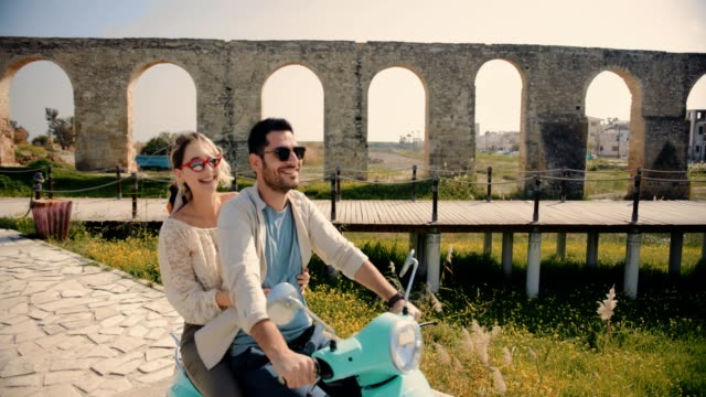 Young friends riding retro scooter next to ancient European monument