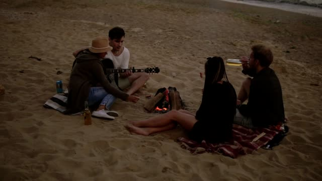 Young friends sitting by the fire on the beach, grilling sausages, drinking beer and playing guitar. Slowmotion shot - video