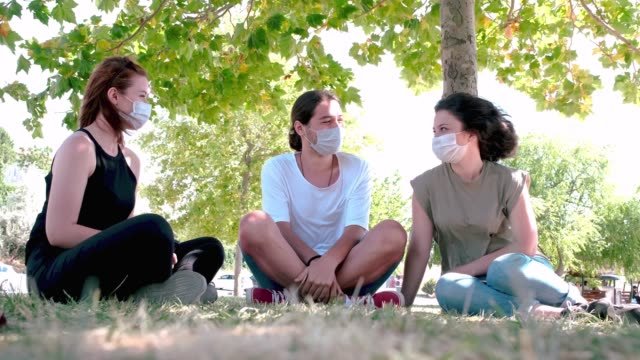 Young friends talking and laughing while sitting on grass. Meeting with friends in the park during the coronavirus epidemic. Following the rules of social distancing and wearing face masks. Young friends talking and laughing while sitting on grass. Meeting with friends in the park during the coronavirus epidemic. Following the rules of social distancing and wearing face masks. holiday event stock videos & royalty-free footage