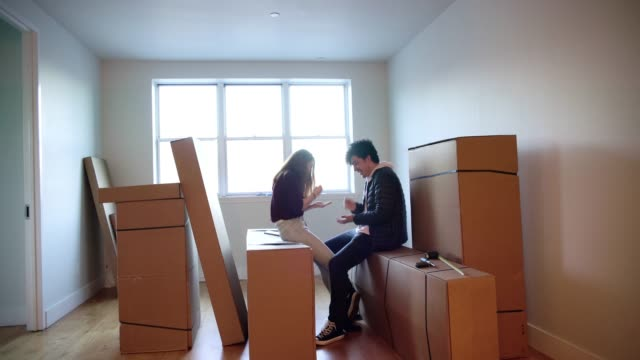 Young friends, teenagers girl and boy, playing, sitting on the card boxes in the living room of the new house. video