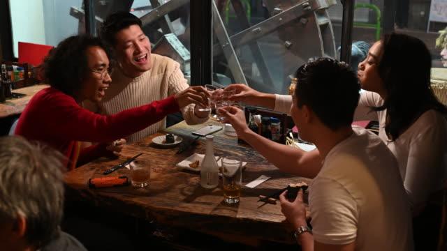vidéos et rushes de jeunes amis grillent et boivent le saki dans l'izakaya japonais - culture japonaise