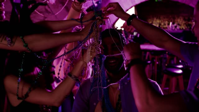 Young friends with colorful beads celebrating Mardi Gras at party video