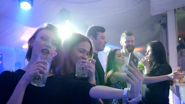 junge freunde frauen hält cocktails in der hand und macht selfie hinter der bar zu begegnen, im nachtclub auf hintergrund der lichter - turngerät mit holm stock-videos und b-roll-filmmaterial