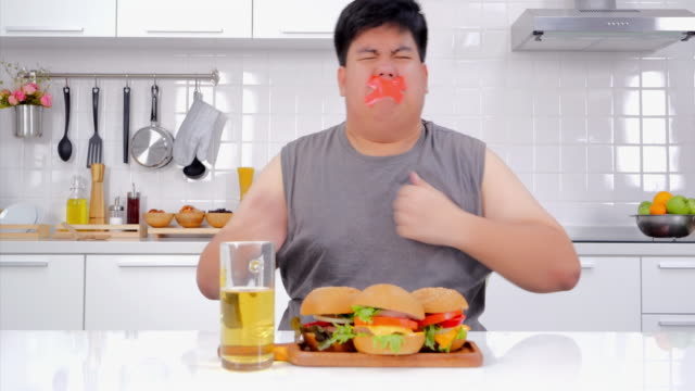 Young frustrated man with a measuring tape around his mouth junk food shaped.Man on diet with a guilty conscience.Diet restriction stress concept.Real Bodies