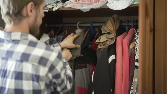 vídeos y material grabado en eventos de stock de joven adolescente frustrado busca una ropa adecuada en el hogar - desordenado