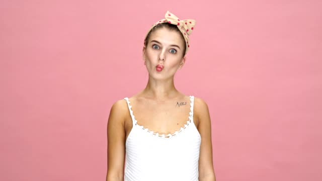 Young funny caucasian lady showing different emotions over pink background. video