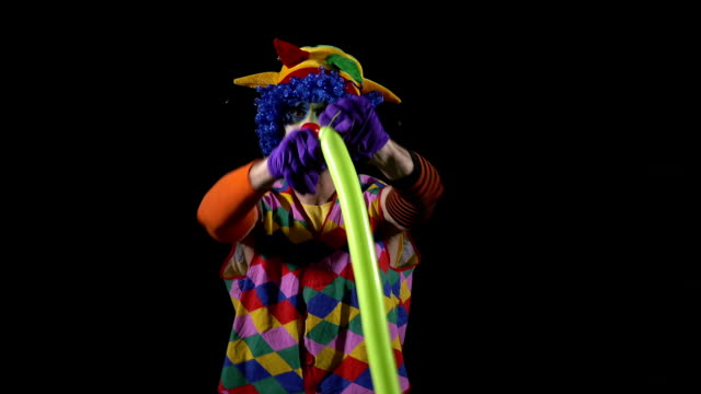 Young funny clown making a sword from a balloon video