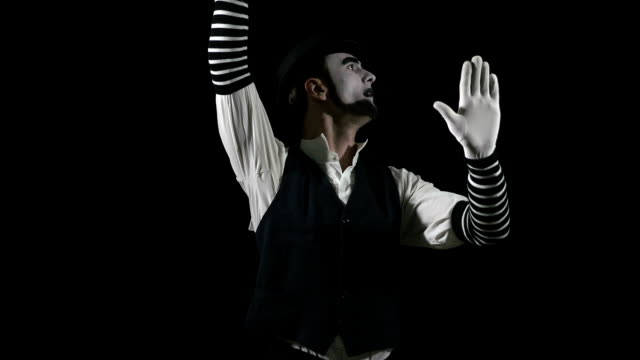 Young funny mime behind an invisible glass box or wall video