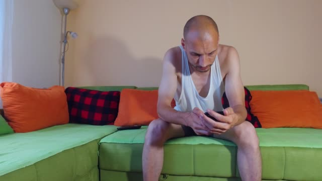 Young funny unemployed single man looking photos of girls on smartphone or mobile phone wasting his time swiping and liking the pictures on the social networks during the day time in his room at home
