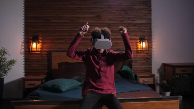 giovane giocatore che si gode la vittoria nel tiro al gioco vr - occhiali protettivi video stock e b–roll