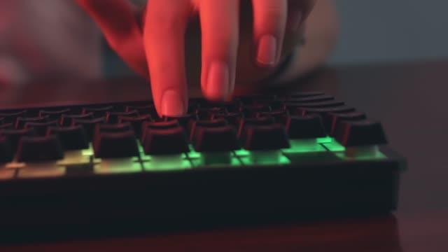 young gamer plays a video game, close-up of hands, player uses gaming keyboard, illuminated coral color and multicolor neon, cybersportsman. - gioco d'azzardo video stock e b–roll