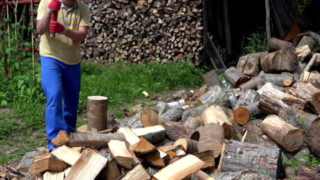 Young gardener man chop wood with axe near woodshed. FullHD video