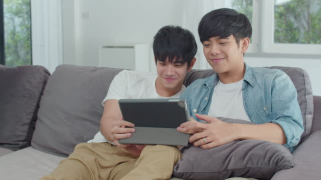 Young Gay couple using tablet at home. Asian LGBTQ men happy relax fun using technology watching movie in internet together while lying sofa in living room concept. Slow motion Shot.