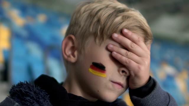 vídeos de stock e filmes b-roll de young german fan upset after match loss, football championship, team support - criança perdida