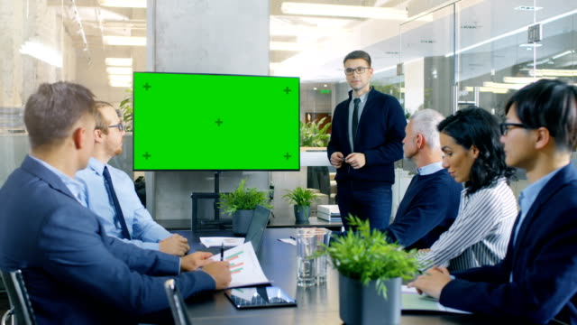 Young Gifted Businessman Gives Report/ Presentation to His Business Colleagues, Pointing at Green Chroma Key Screen Wall TV. Young Gifted Businessman Gives Report/ Presentation to His Business Colleagues, Pointing at Green Chroma Key Screen Wall TV. Shot on RED EPIC-W 8K Helium Cinema Camera. presentation stock videos & royalty-free footage