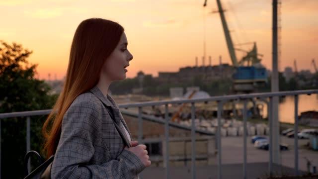 stockvideo's en b-roll-footage met jonge gember vrouw in jas lopen over de brug, industriële fabriek achtergrond, zonsondergang - men blazer