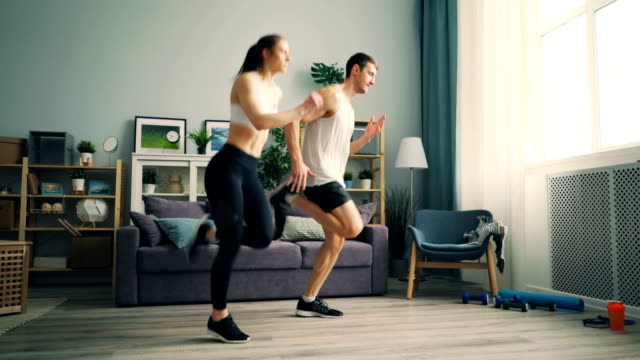 Young girl and guy in sportswear running at home doing sports together training