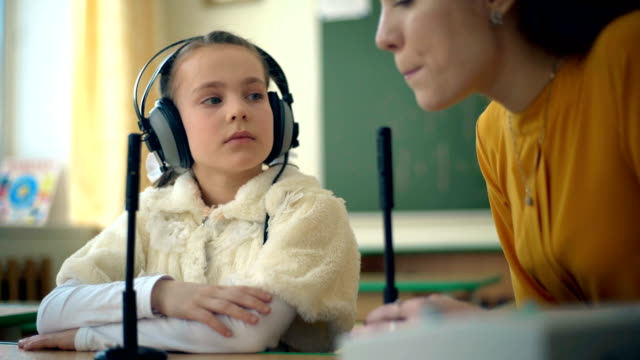 young girl and teacher using headphones and microphone in the classroom - sordità video stock e b–roll