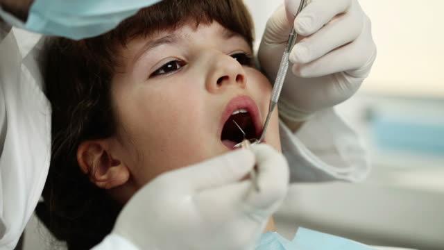 vídeos y material grabado en eventos de stock de chica joven en el dentista - ortodoncista