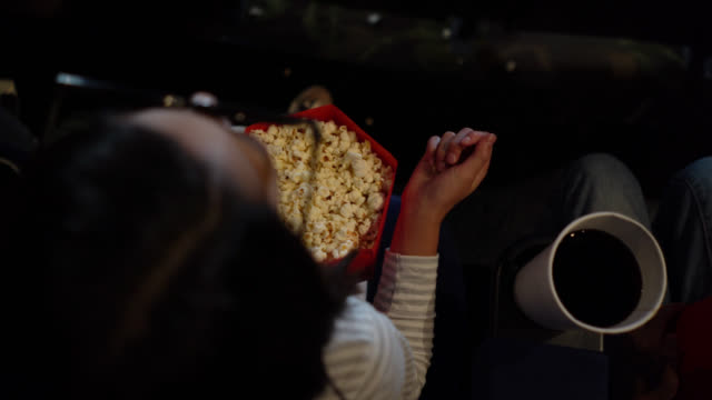 Young girl at the movies enjoying popcorn while watching a 3D movie video