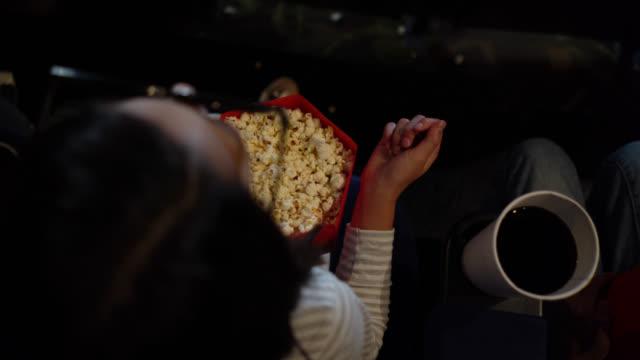 stockvideo's en b-roll-footage met jong meisje op de films genieten van popcorn tijdens het kijken naar een 3d-film - popcorn