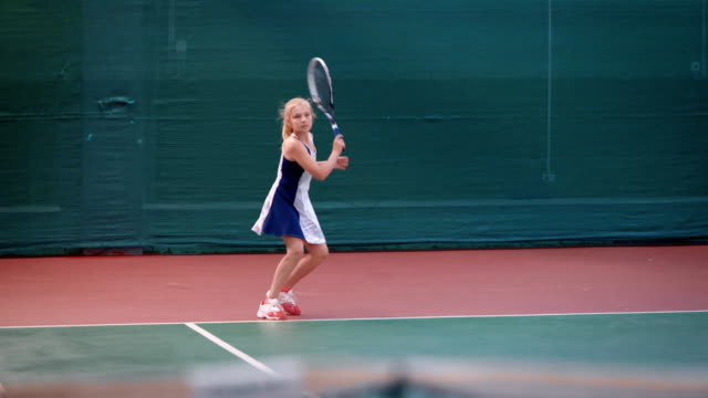 Young girl athlete in a sportive form actively discourages tennis balls professional racket during training on the sports field video