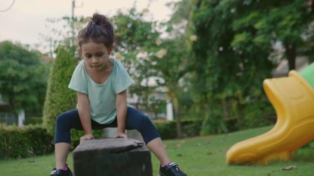 Young Girl Balances in garden.