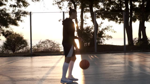 stockvideo's en b-roll-footage met jong meisje basketballer wandelen door basketbalveld buiten in de ochtend tijdens het stuiteren van de bal. zijaanzicht - basketbal teamsport