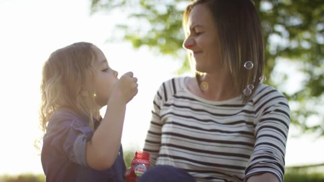 Young Girl Blowing Bubbles With Her Mother video